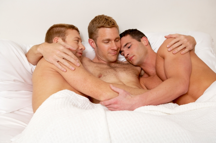 Three gay men in bed together.